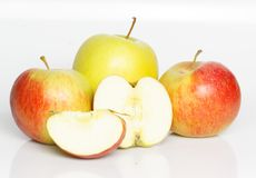 Four apples. One big, yellow apple and two smaller, red apples with one appel cut open Stock Images