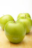 Four Apples. Four green apples on a cutting board Royalty Free Stock Photography