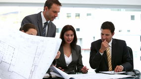 Four architects looking at plans at a table Royalty Free Stock Images