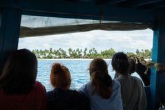 Four Asian women looking out of the ferry boat to the paradise beach of Koh Mook, Thailand royalty free stock photography
