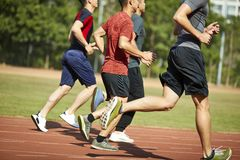 Asian young adults running on track. Four asian young adults training running on track Stock Image