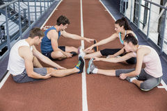 Four athletic women and men stretching. On running track Stock Photo