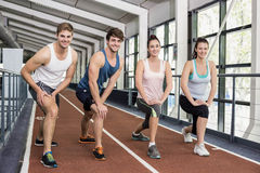 Four athletic women and men stretching. On running track Stock Images