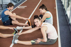 Four athletic women and men stretching. On running track Royalty Free Stock Photo