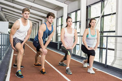 Four athletic women and men stretching. On running track Stock Image
