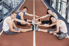 Four athletic women and men stretching. On running track Royalty Free Stock Image