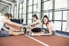 Four athletic women and men stretching. On running track Royalty Free Stock Photography