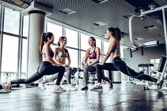Four athletic woman performing low fallouts in gym with panoramic windows background. Four athletic women performing low fallouts in gym with panoramic windows stock images