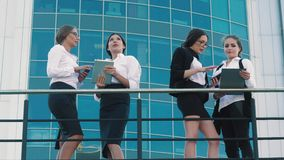Four attractive female coworkers standing outdoors and chatting. They look interested and enjoy their time off stock video footage