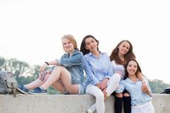 Four attractive happy cute female friends sitting in nature and looking camera stock photos