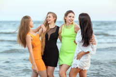 Four attractive young women standing on a sea background. Pretty ladies in bright dresses smiling and laughing. Girls on. Charming and young women in cocktail stock photos