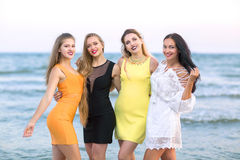 Four attractive young women standing on a sea background. Pretty ladies in bright dresses smiling and posing. Girls on stock images