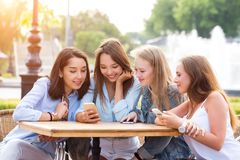 Four attractive young women use smartphones at a table royalty free stock photos