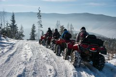Four ATV riders on off-road quad bikes in the winter mountains. Four ATV riders on off-road quad bikes on snow in the winter mountains Stock Photo