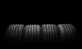 Four automobile rubber tires isolated on black Stock Photography