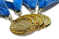 Four award medals of gold color with blue ribbons Stock Photos