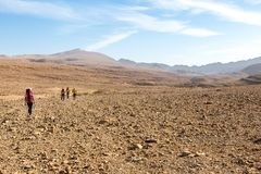 Four backpackers hiking trail, Negev desert, Israel. stock photography
