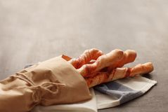 Four baguettes in wrapping paper tied with twine lie on the table Stock Images