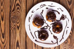 Four baked cupcakes with chocolate cream on white ceramic dish on old rustic brown weathered table stock photography
