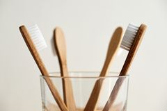 Four bamboo toothbrushes in a glass royalty free stock image