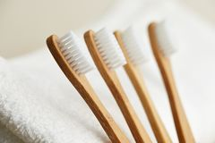 Four bamboo toothbrushes on white towel royalty free stock images