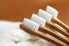 Four bamboo toothbrushes on white towel stock photo