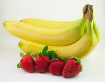 Four bananas and four strawberries on the the white background. Four bananas and four strawberries  isolated with the white background Royalty Free Stock Image
