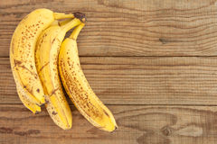 Four bananas on wooden table Royalty Free Stock Photo