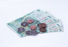 Four banknotes worth 1 Romanian Leu with several coins worth 10 and 5 Romanian Bani  on a white background Royalty Free Stock Photography