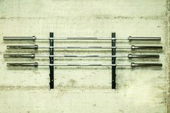 Four barbell weight bars on the stand screwed on the grunge wall prepared for bodybuilding weightlifting sport in the gym. Four barbell weight bars on the stand Royalty Free Stock Images