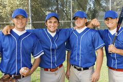 Four baseball team-mates posing on field Stock Photo