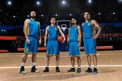 Four basketball players on basketball court. Four basketball players standing on basketball arena Royalty Free Stock Image