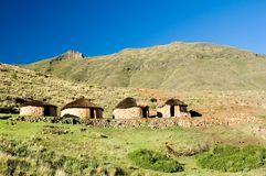 Four Basotho Huts. A Traditional sandstone Basotho rondavel with coloured outline of door frames in remote mountain setting Stock Photo
