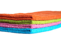 Four bath towels of different colors stacked isolated Stock Photography
