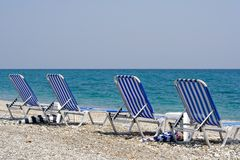 Four Beach Chairs. In front of the ocean deep blue (the Aegean Sea in Greece royalty free stock image