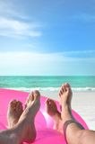 Four beach feet on pink ring Royalty Free Stock Images