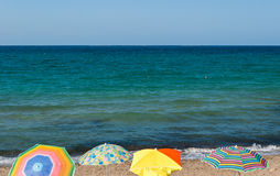 Four beach umbrellas in a beach of Sicily during the summer Stock Photo