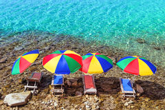 Four beach umbrellas and sunbeds in the water Royalty Free Stock Images