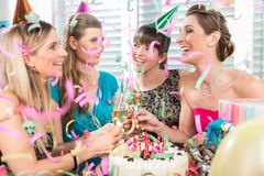 Four beautiful and cheerful women toasting with champagne. Four beautiful and cheerful women smiling while toasting with champagne during a surprise birthday royalty free stock images