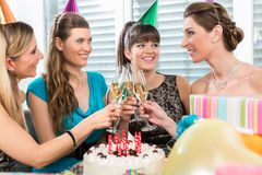 Four beautiful and cheerful women toasting with champagne. Four beautiful and cheerful women smiling while toasting with champagne during a surprise birthday royalty free stock photo