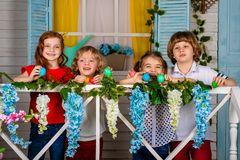 Four beautiful children, two boys and two girls stand on a wooden threshold and laugh royalty free stock images