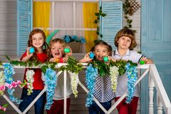 Four beautiful children, two boys and two girls stand on a wooden threshold and laugh stock photography
