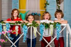 Four beautiful children, two boys and two girls stand on a wooden threshold and laugh stock images
