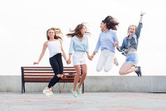 Four beautiful crazy joyful girlfriends jumping and having fun in park royalty free stock images