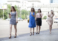 Four beautiful fashion girls walking on the street Royalty Free Stock Photos