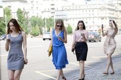 Four beautiful fashion girls walking on the street Royalty Free Stock Image