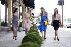 Four beautiful fashion girls walking on the street Stock Photos