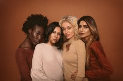 Multi ethnic group of women. Four beautiful girl friends standing together on brown background. Multi ethnic group of women in studio looking at camera royalty free stock image