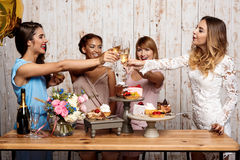 Four beautiful girls clinking glasses with champagne at party. Stock Images