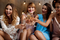 Four beautiful girls clinking glasses with champagne at party. Four young beautiful girls in dresses smiling, laughing, clinking glasses with champagne at party Royalty Free Stock Photo